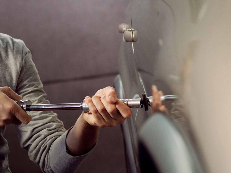 Un addetto VW Service mentre ripara una carrozzeria - Clever Repair.