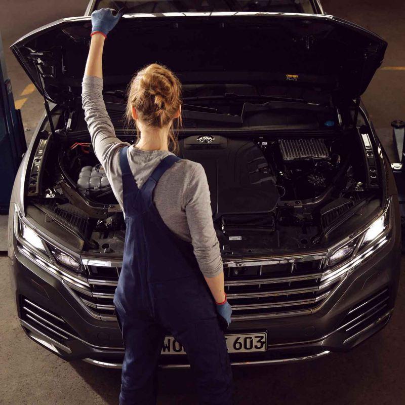 Un meccanico di Volkswagen Service ispeziona il motore di un'auto VW.