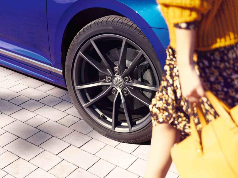 Dettaglio della ruota di un'auto Volkswagen con cerchi in lega neri.