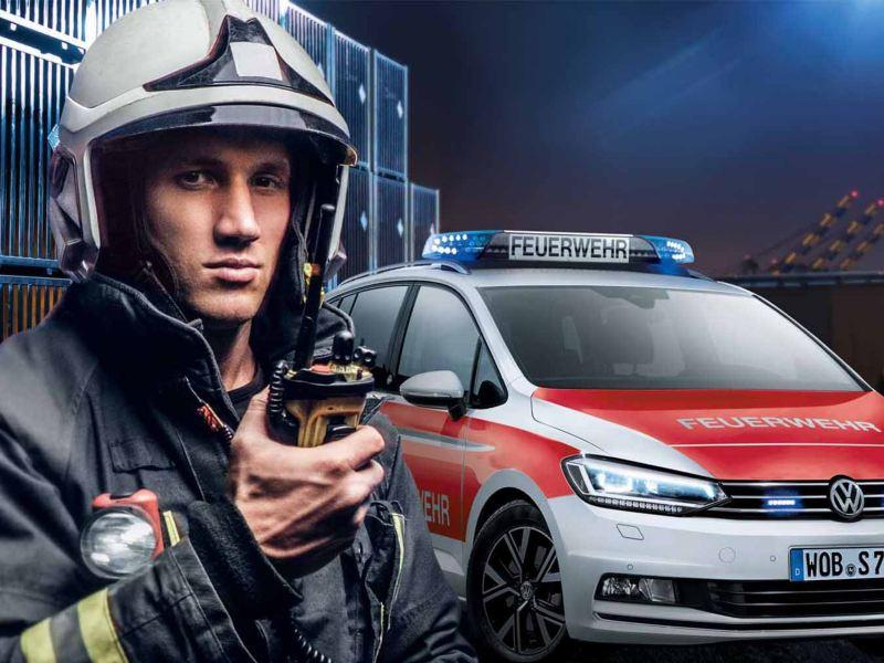Un vigile del fuoco davanti alla sua Volkswagen adibita ad auto di emergenza, pronto a intervenire in caso di necessità