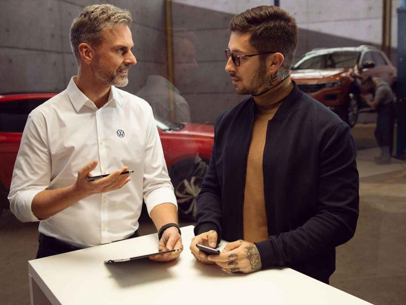 Un addetto Volkswagen illustra a un cliente i piani di manutenzione della sua auto