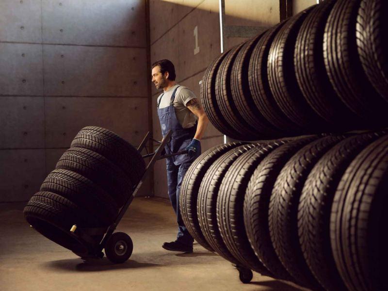 Un operaio di Volkswagen Service trasporta una pila di pneumatici su un carrellino.