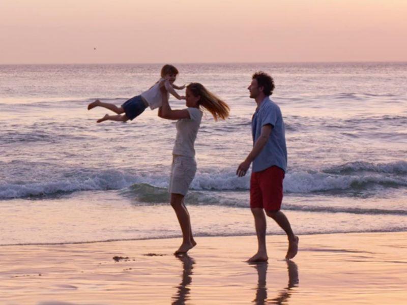 Una famiglia passeggia in riva al mare, la madre solleva in aria il bambino.