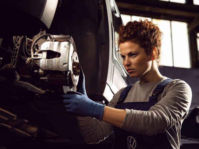 Un meccanico Volkswagen Service sostituisce i freni dell'auto.