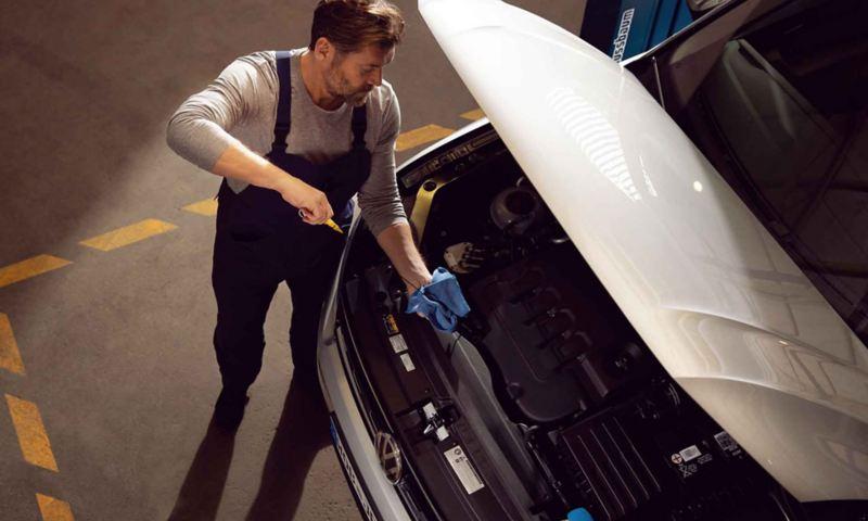 Un meccanico di Volkswagen Service controlla il livello dell'olio motore di un'auto VW.
