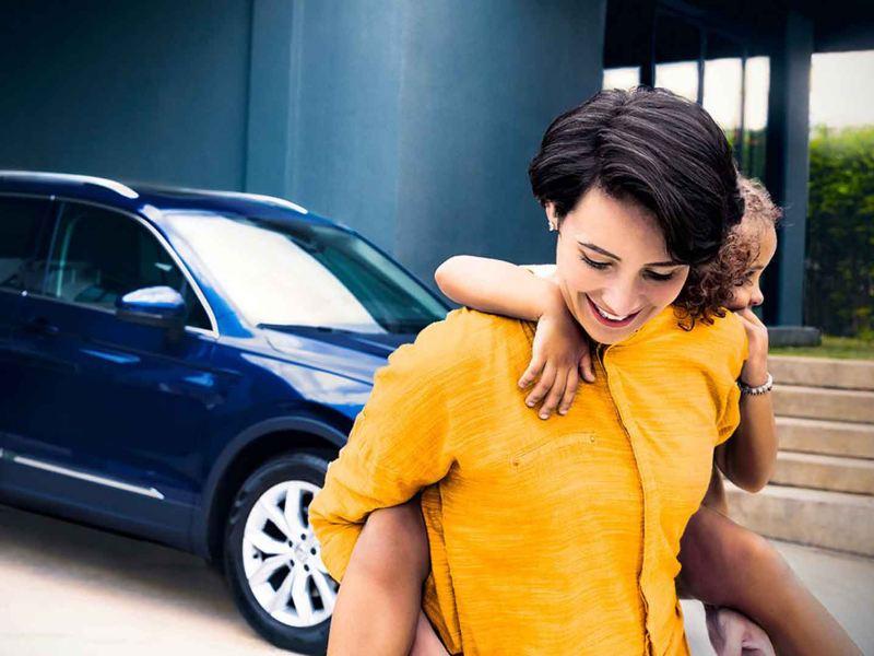 Una donna con in spalla sua figlia si allontana dalla sua auto Volkswagen