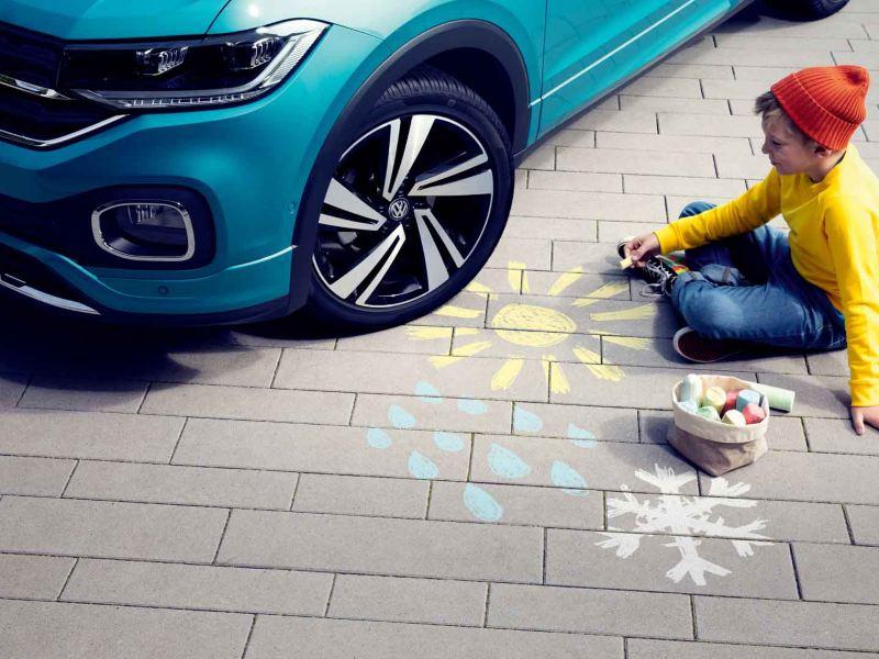 Bambino che disegna per terra coi pastelli colorati, a fianco ad una Volkswagen. Con dettaglio del cerchio in lega e del pneumatico Volkswagen Plus.