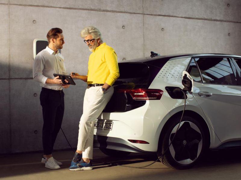 Un impiegato Volkswagen e un cliente parlano accanto ad una ID.3 in carica