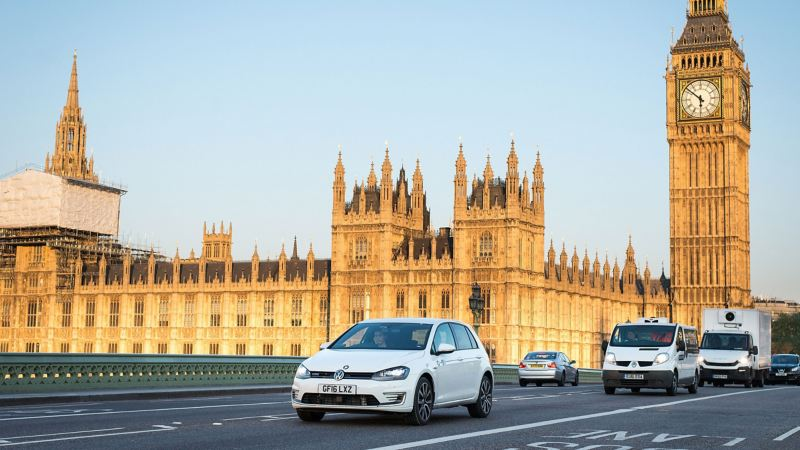 A Golf GTE on a London road the Palace of Westminster