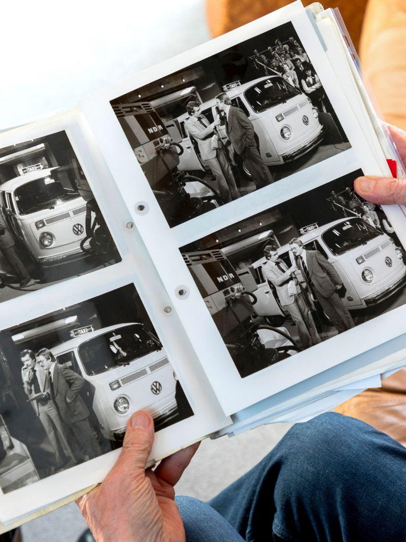 Dr. Kalberlah looking at a photo album of the T2 Elekro camper