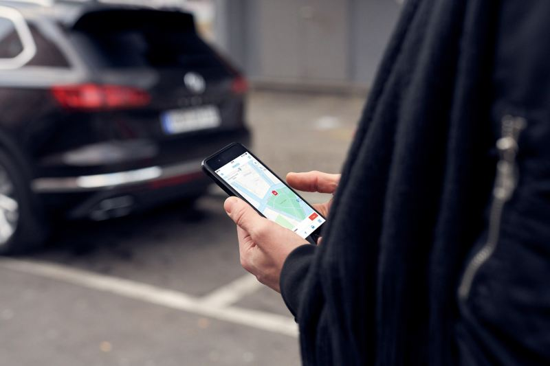 A man holds his mobile phone, the screen displays the We Park app