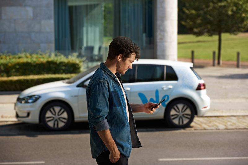 A man looking down at his phone stands in the foreground in front of an e-golf