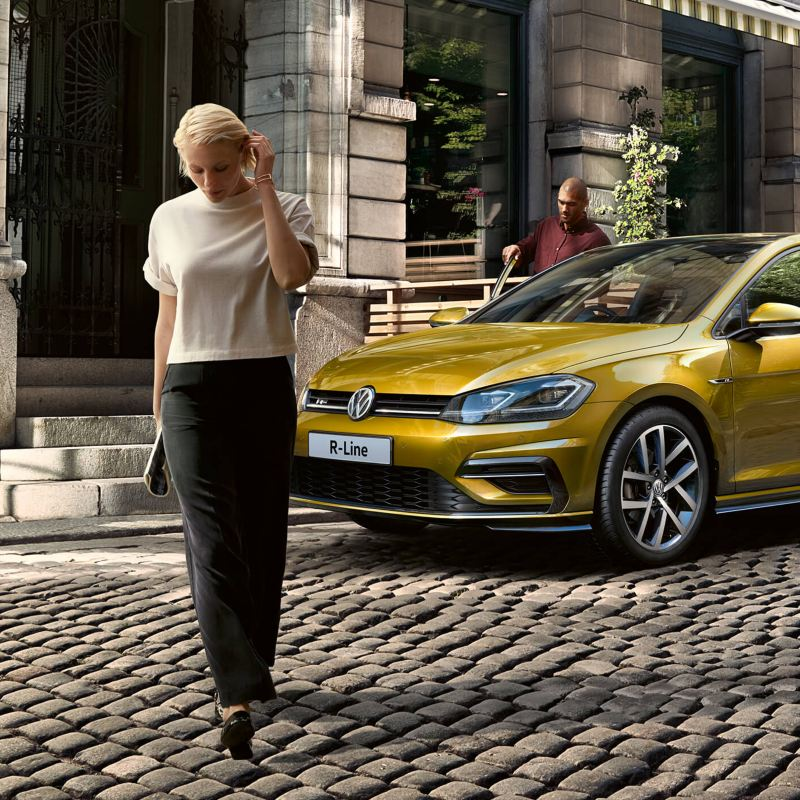 Woman standing in front of a Volkswagen car