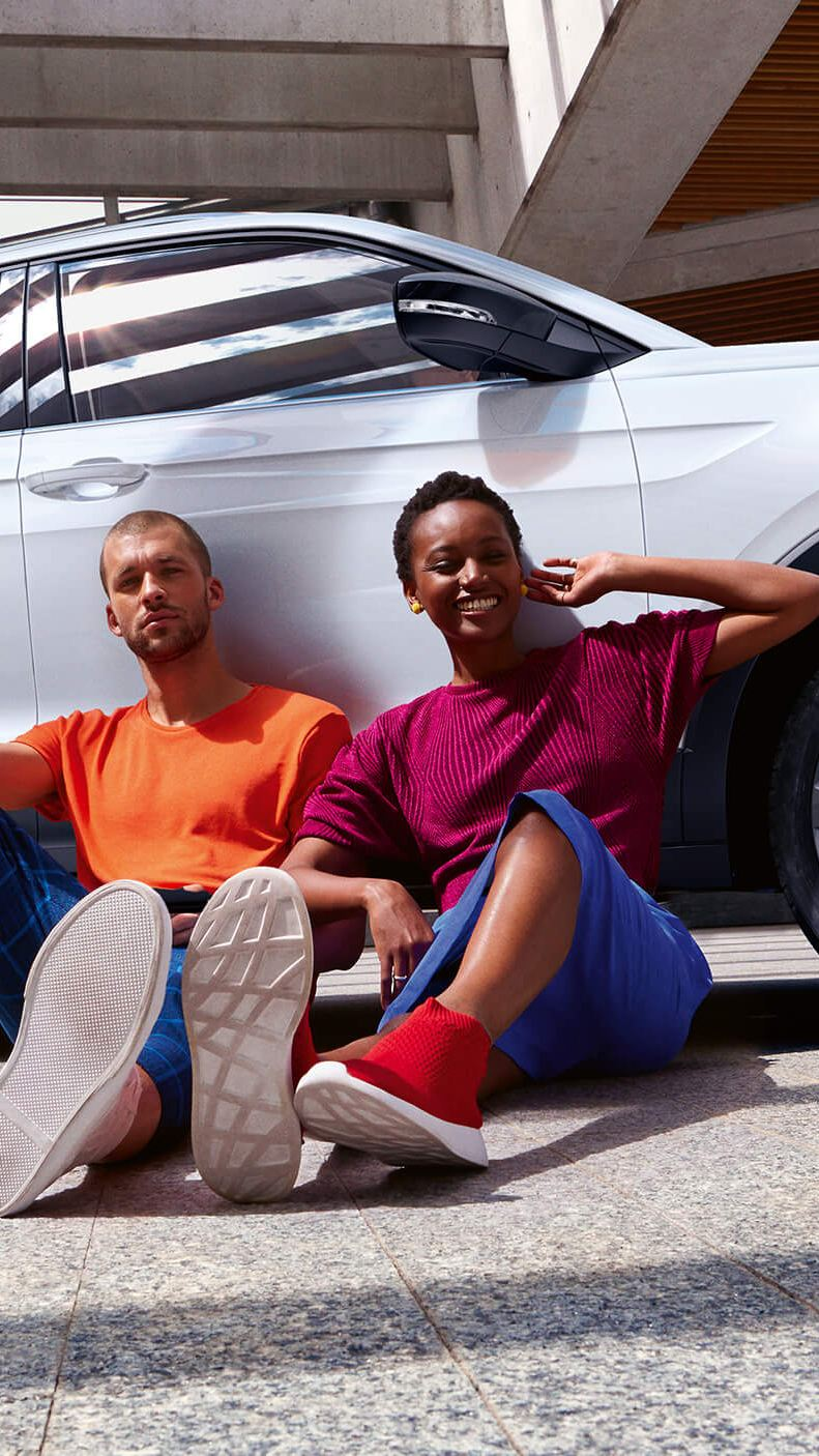 Couple sat on the ground leaning against their car