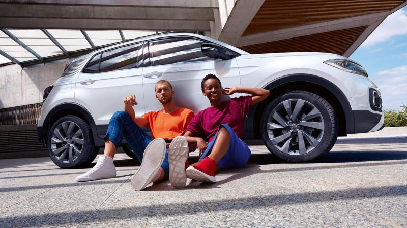 A couple sitting on the side of a Volkswagen car