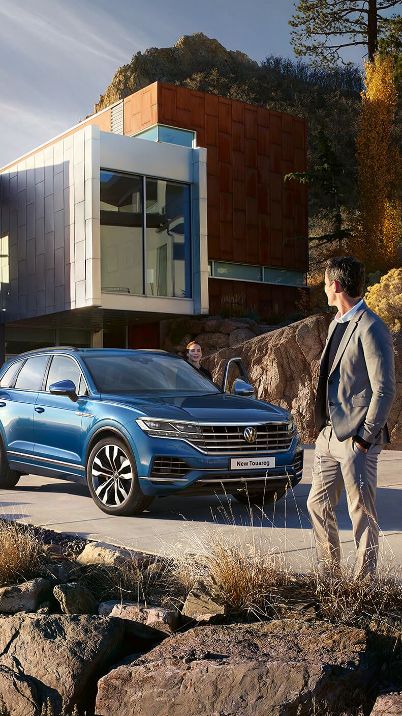 A blue new Touareg parking in front of a house with a lady and a man