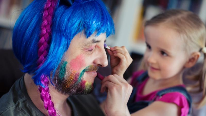 A child applying face paint to a man's face