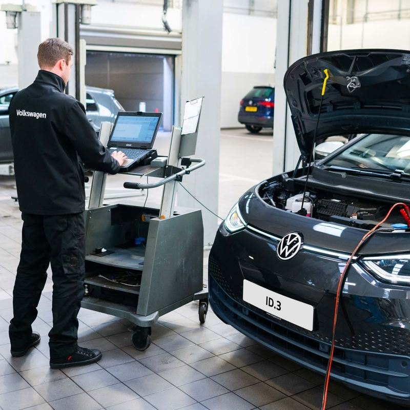 A technician typing into a computer plugged into a VW ID.3