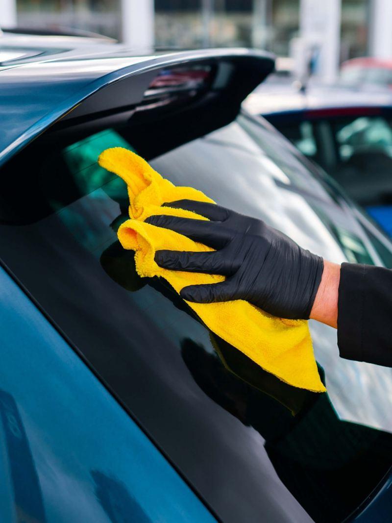 A service employee polishing the rear windscreen on a blue VW car