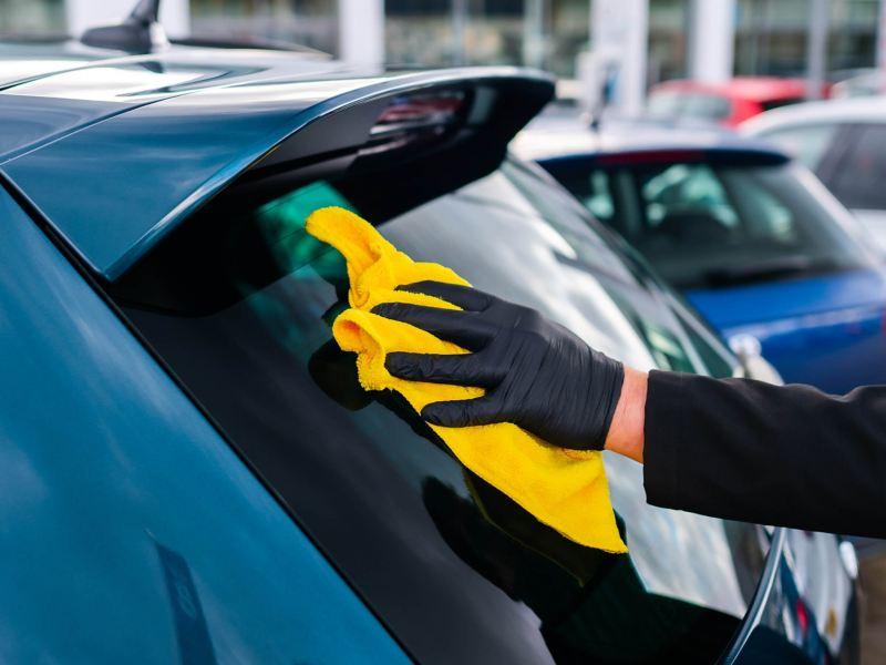 A service employee polishing the rear windscreen on a blue VW
