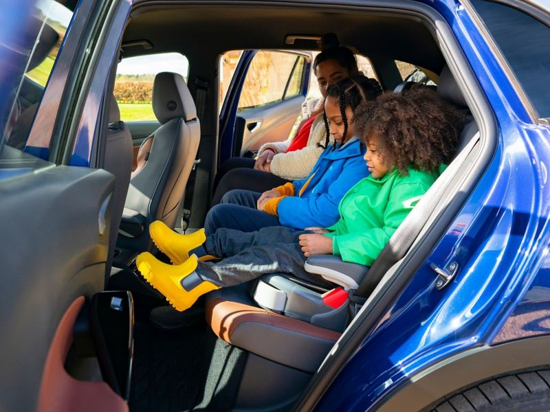 2 children on booster seats next to their parent in the rear of a VW ID.4