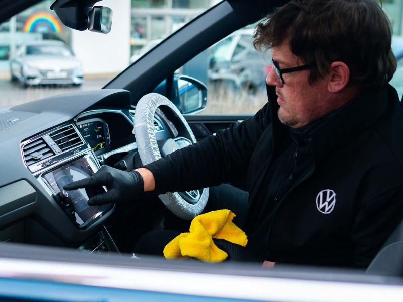 A service employee sits inside a VW pressing on the infotainment screen