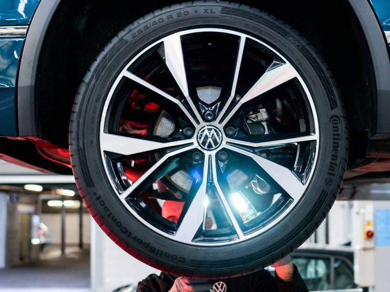 A VW service employee shining a light through the back of a tyre