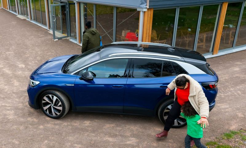 A family walking around a blue VW ID.4 parked outside a cafe