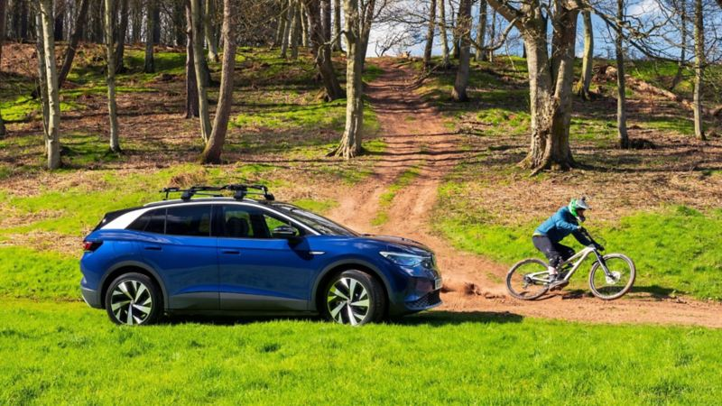 A parked blue VW ID.4 in a forest with a mountain biker in front