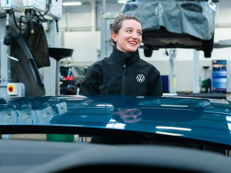 A VW service employee holding the bonnet on a car