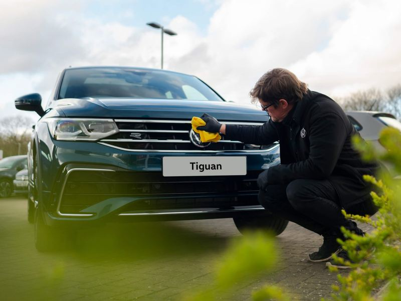 A service employee polishing the front badge on a blue VW Tiguan