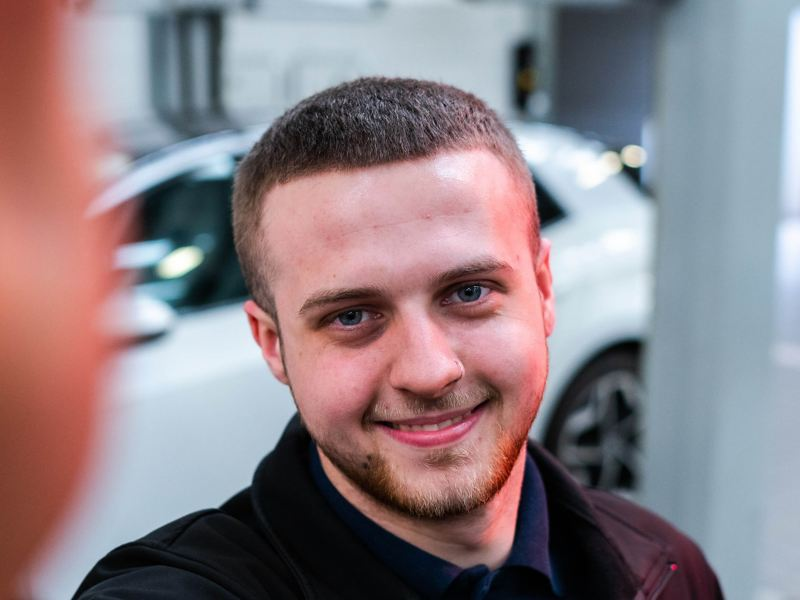 A VW service employee smiling holding paperwork