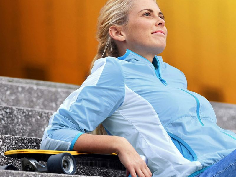 woman sitting on steps with a skateboard