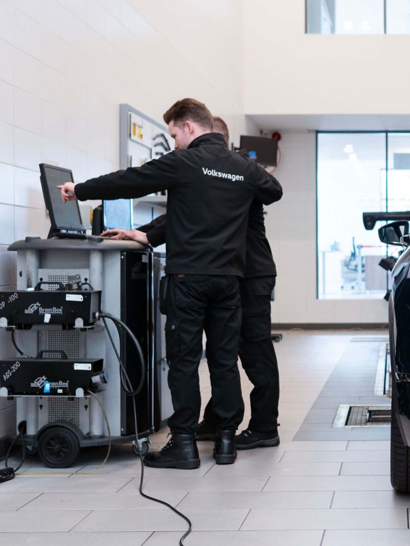 Two VW technicians stand at a computer with a blue VW Tiguan beside them