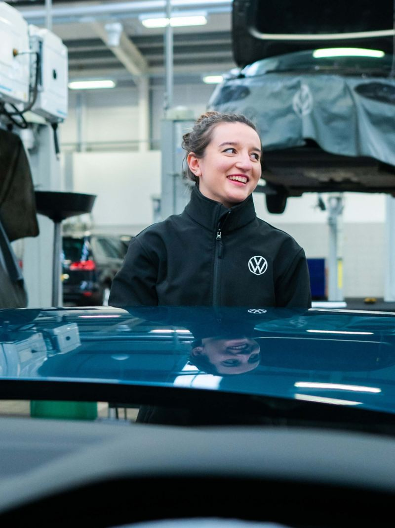 A VW technician stands in front of a blue bonnet smiling