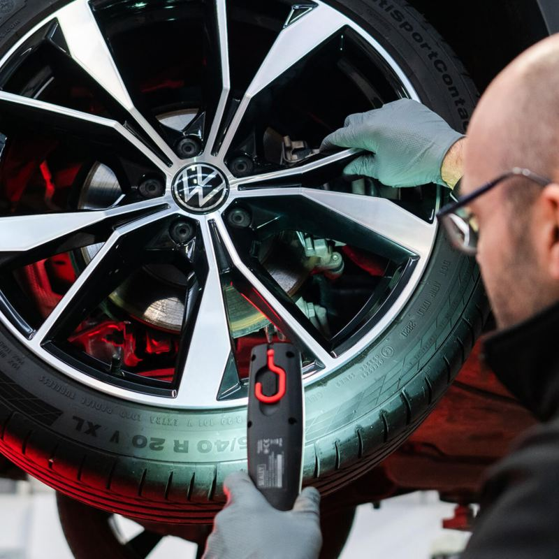 A VW technician inspecting a tyre with a light