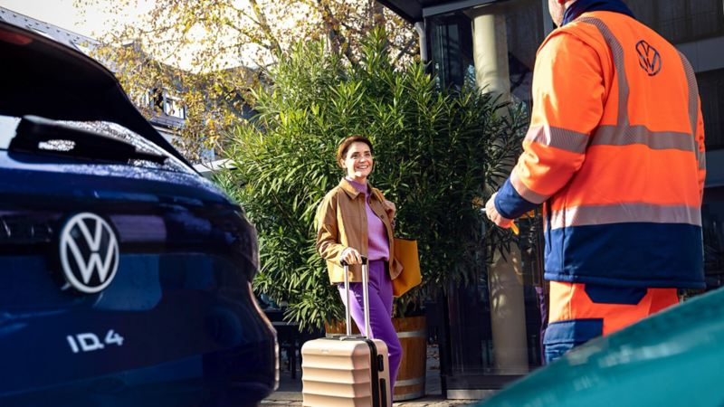 A person wheeling a suitcase being greeted by a VW roadside assistance technician