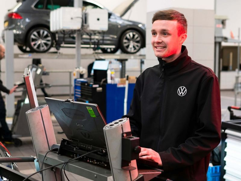 A VW technician typing into a computer in a workshop