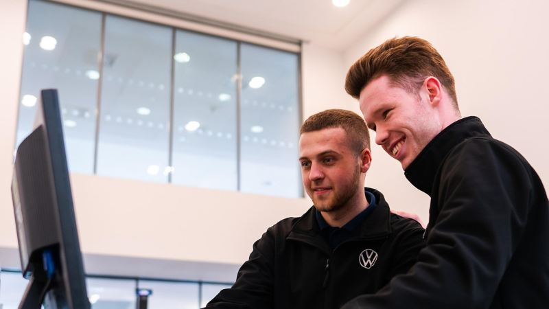 Two VW technicians standing at a computer