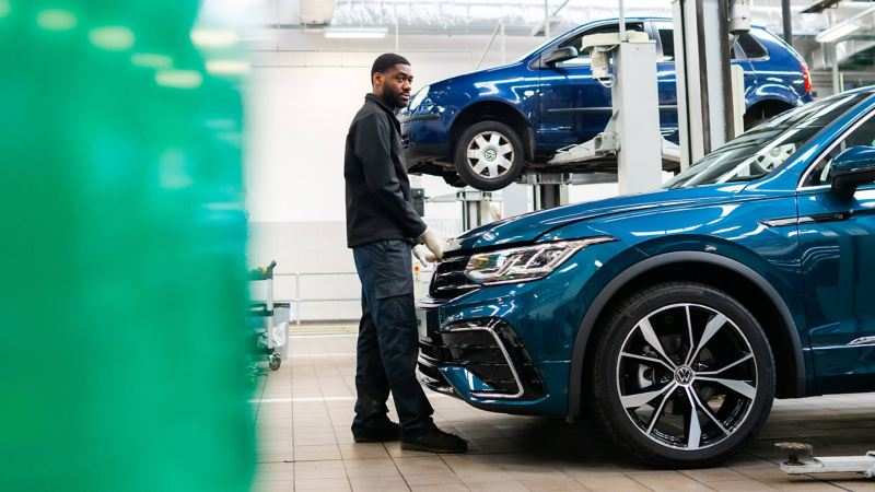 A technician holding about to open the bonnet of a blue VW Tiguan