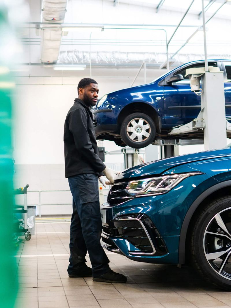 A technician stands at the front of a blue VW with hands on the bonnet