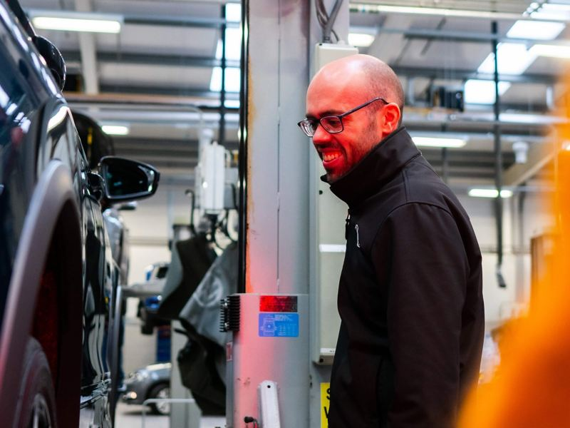A technician with glasses lit by a red light looks at a VW