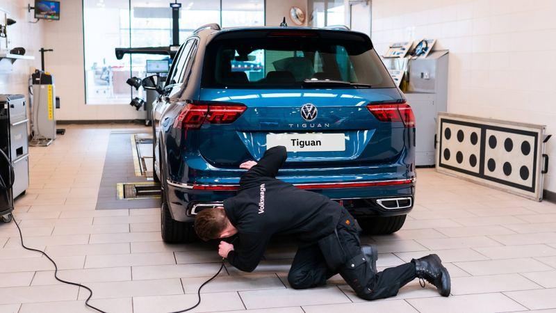 A technician knelt on floor at rear of blue VW Tiguan