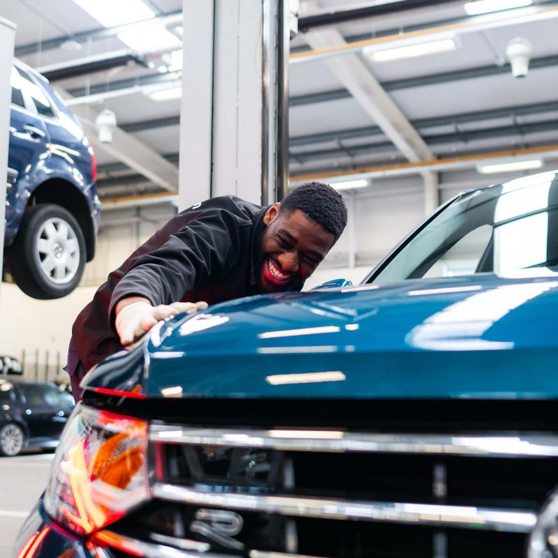 A technician inspecting the paintwork on a blue VW Tiguan