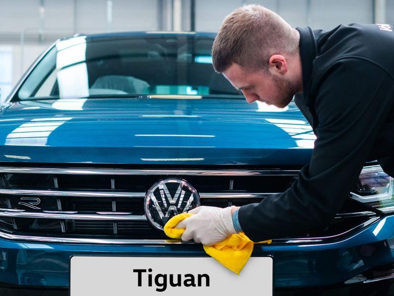 A technician buffering the front VW logo on a blue Tiguan
