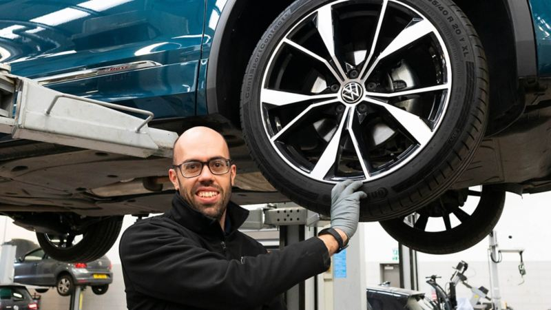 A VW technician wearing a glove with hand on a tyre
