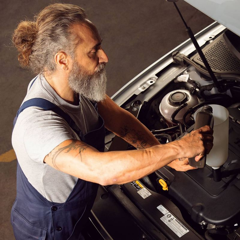 A technician pouring oil into a VW engine