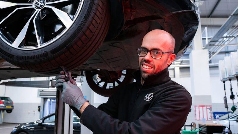 A Volkswagen technician checking a tyre tread