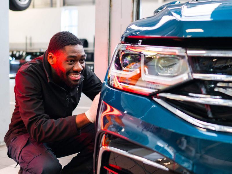 A VW technician inspects the bodywork on a car