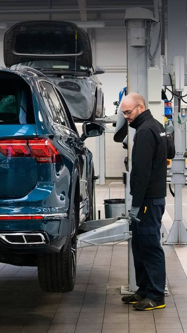 A technician stands next to a ramp raising a blue VW Tiguan